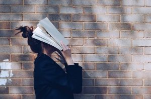 Dziewczyna zasłaniająca twarz książką