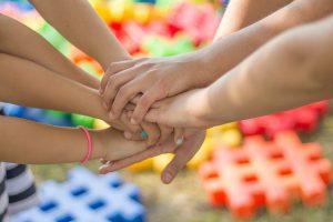 Splecione ręce na tle kolorowych puzzli