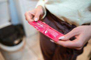 Kobieta trzymająca różowe opakowanie testu ciążowego
